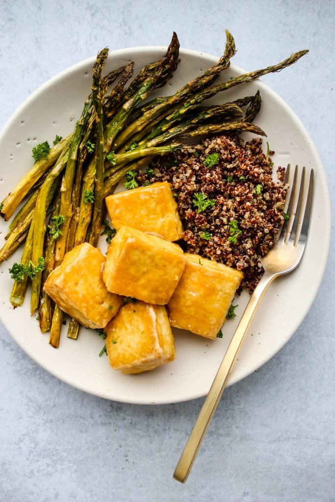 crispy baked tofu topped in maple miso sauce, asparagus, and quinoa on white plate