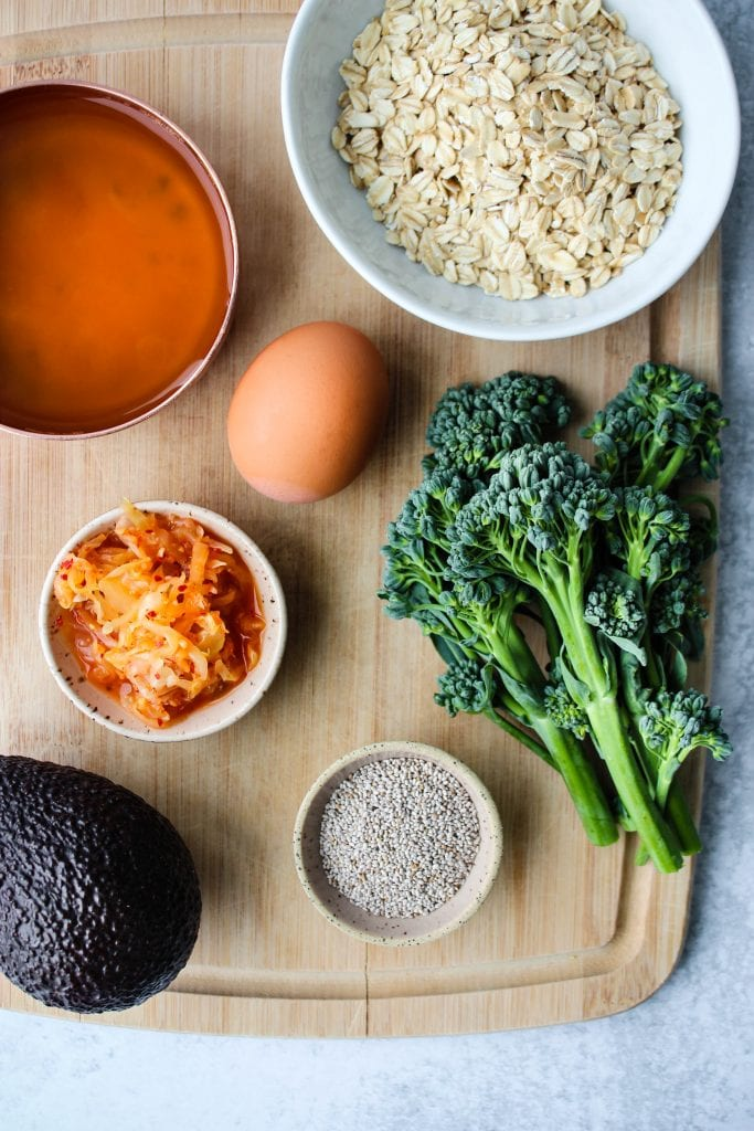 wooden cutting board with broth, oats, egg, kimchi, chia seeds, avocado, broccolini