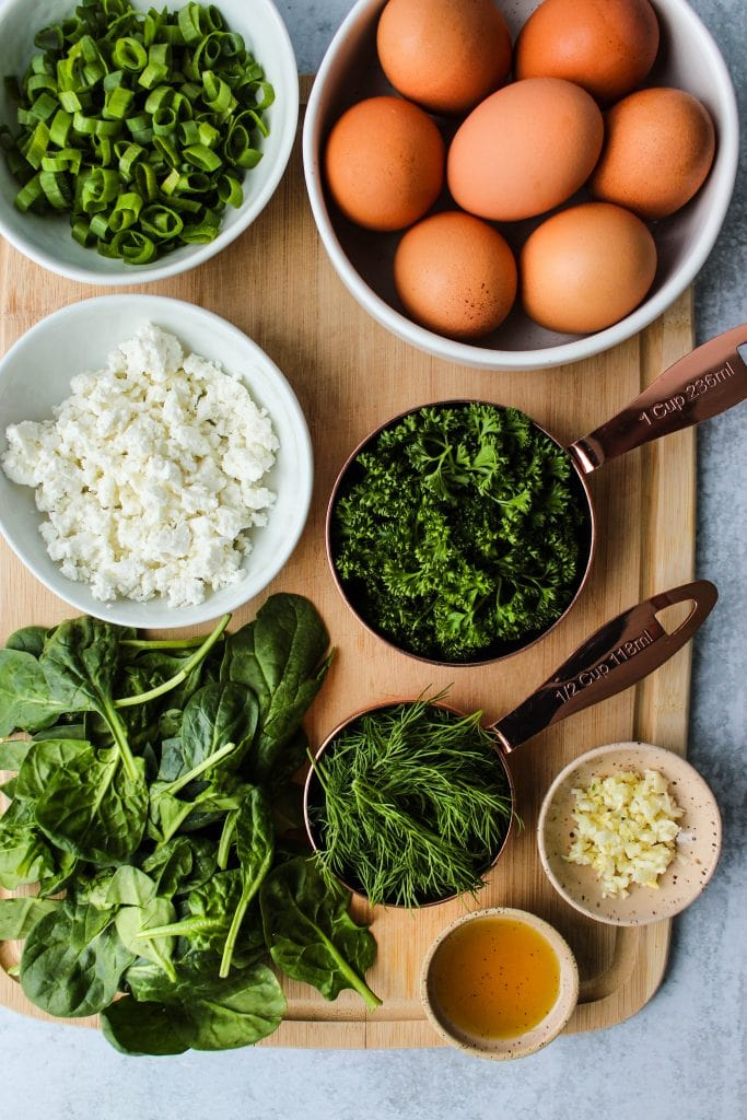 wooden cutting board with eggs, herbs, spinach, and feta cheese in bowls