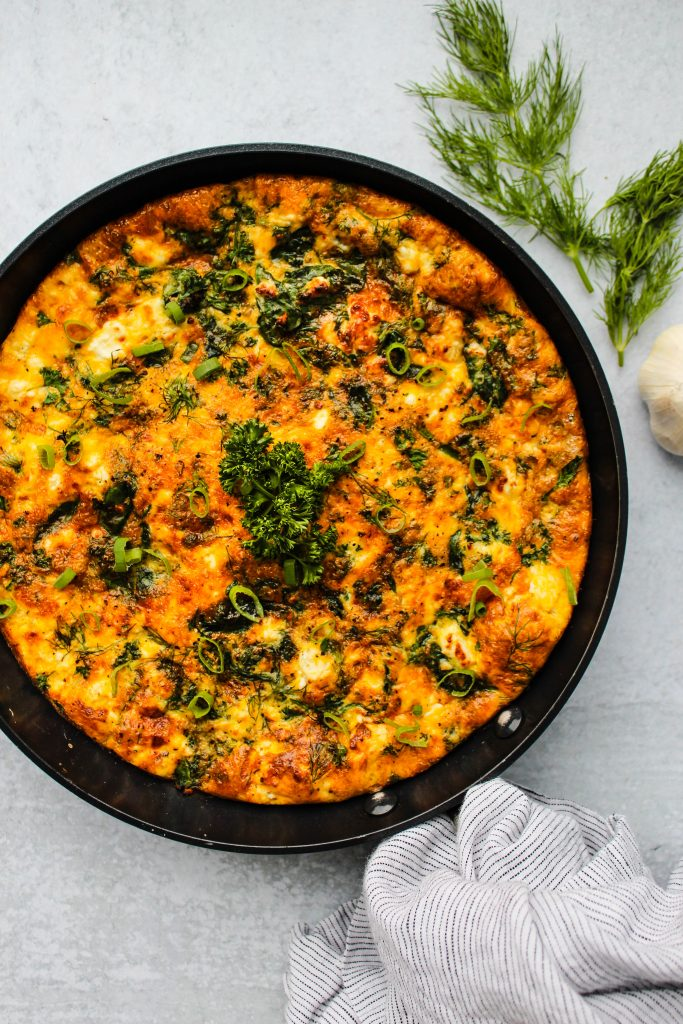 frittata in skillet with spinach, feta cheese, and herbs