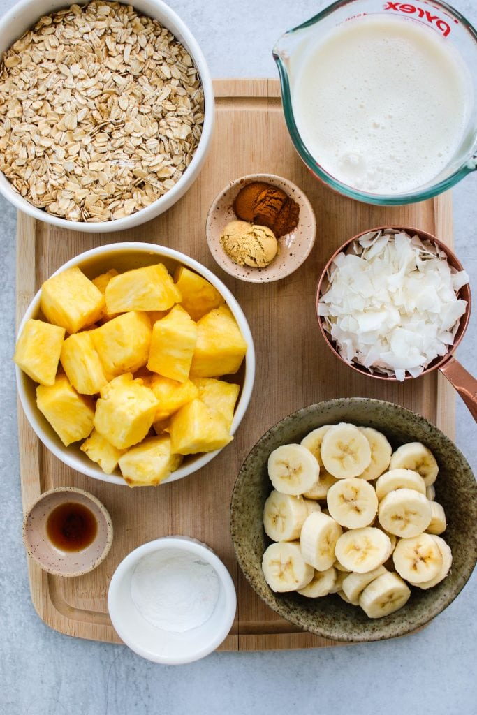 overhead shot of wood cutting board with bowls of oats, milk, spices, pineapple, banana, and coconut