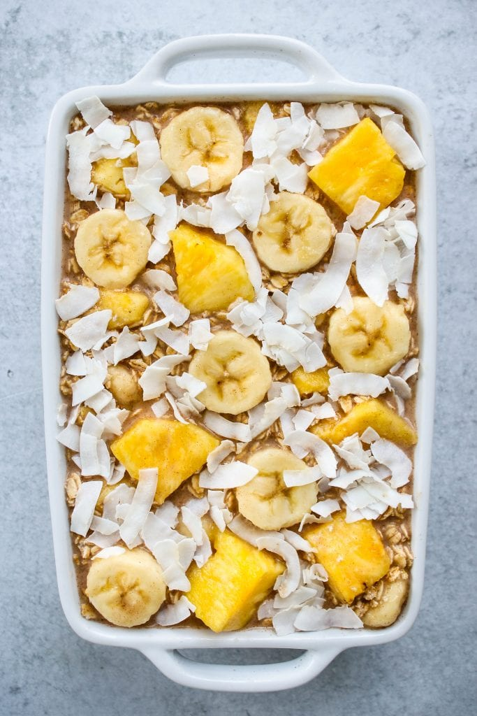 overhead shot of white baking dish with uncooked pineapple, banana, and coconut oatmeal