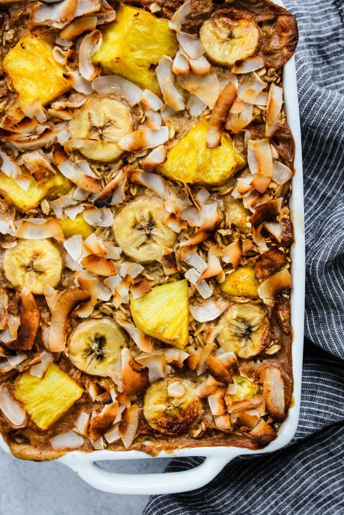 close up shot of white baking dish with pineapple, banana, and coconut baked oatmeal