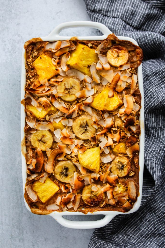 overhead shot of white baking dish with pineapple, banana, and coconut baked oatmeal