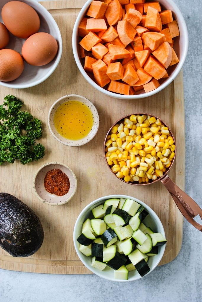 wood cutting board with bowls of sweet potato, eggs, corn, zucchini, oil, taco seasoning, and avocado