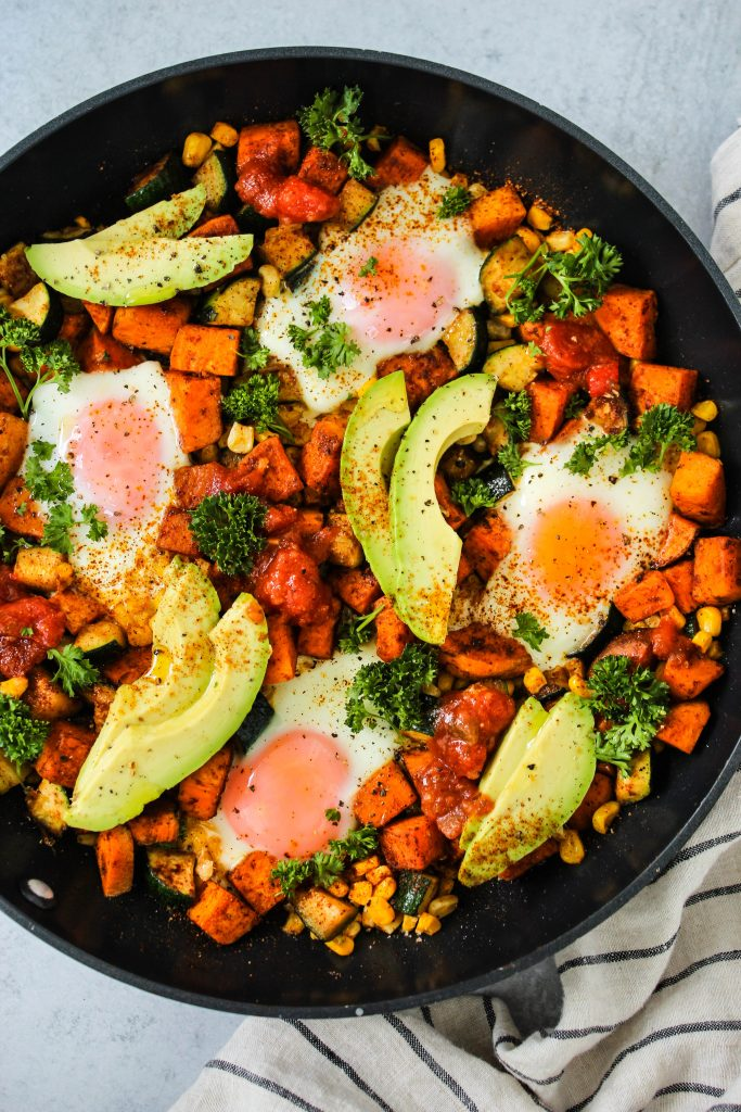 overhead shot of black skillet with sweet potatoes, corn, zucchini, eggs, and avocado slices