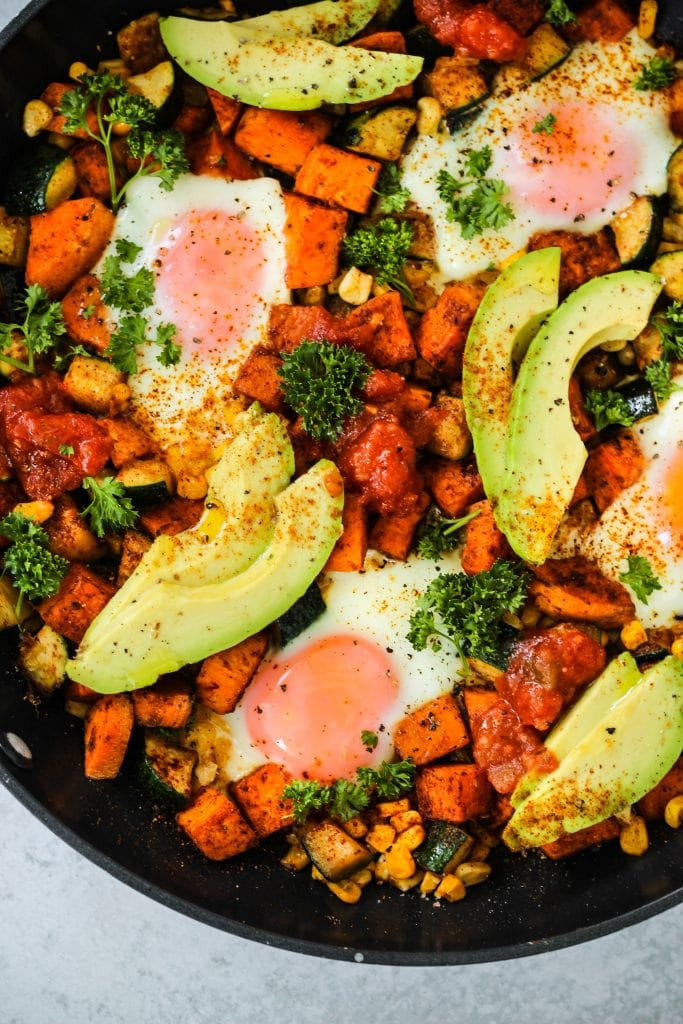 closeup shot of black skillet with sweet potatoes, corn, zucchini, eggs, and avocado slices