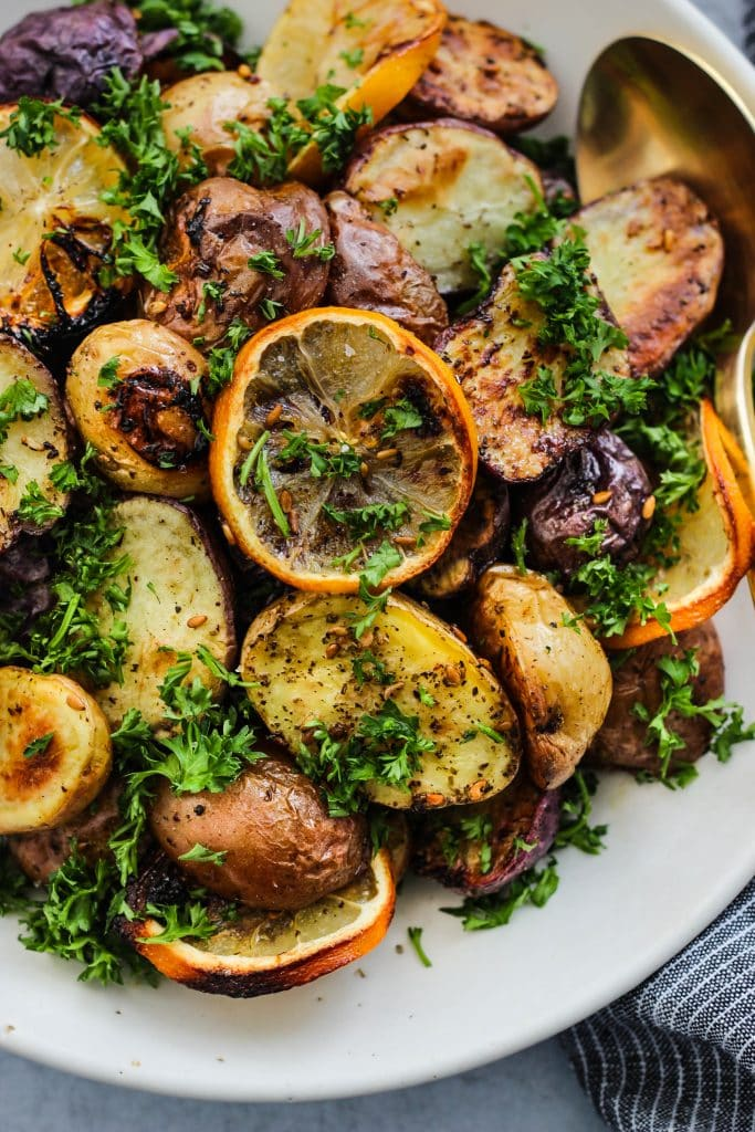 closeup shot of roasted mini potatoes with lemon, za'atar, and parsley in white bowl