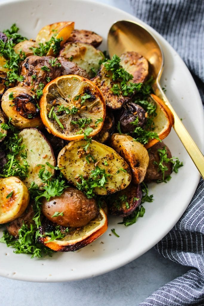 closeup shot of roasted mini potatoes with lemon, za'atar, and parsley in white bowl and gold spoon