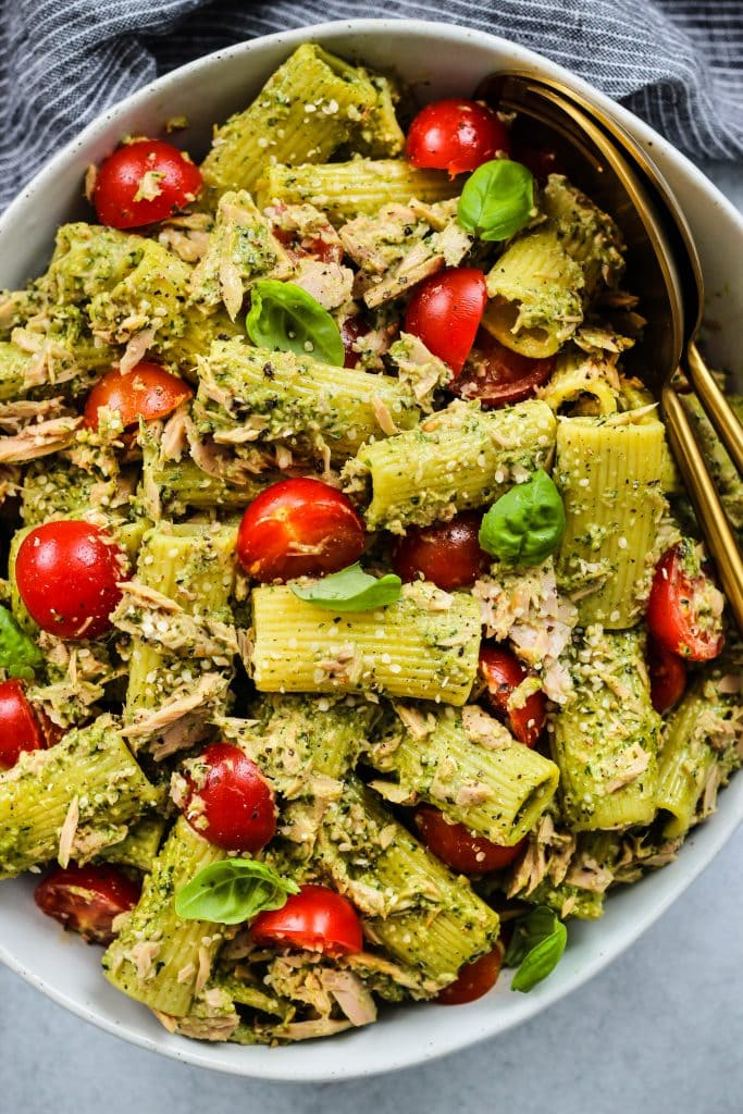 overhead shot of large white bowl with tuna pasta salad, pesto, cherry tomatoes