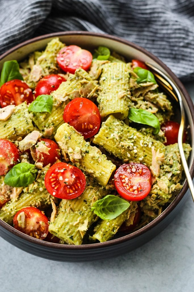 small brown bowl with tuna pasta salad, pesto, cherry tomatoes