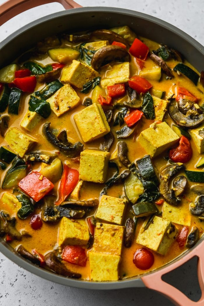 Coconut curry with tofu and vegetables in a large pan.