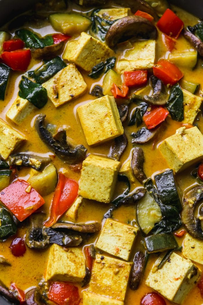 Closeup photo of coconut curry with tofu cubes and chopped vegetables.