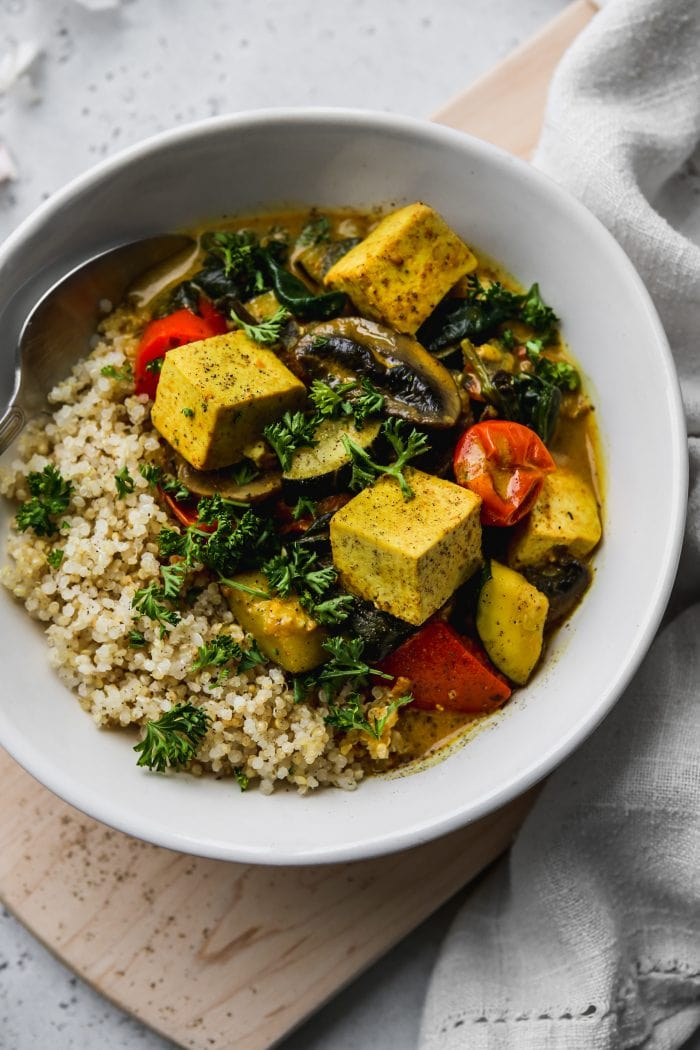 Closeup photo of a white bowl filled with quinoa, tofu, vegetables, and coconut curry.