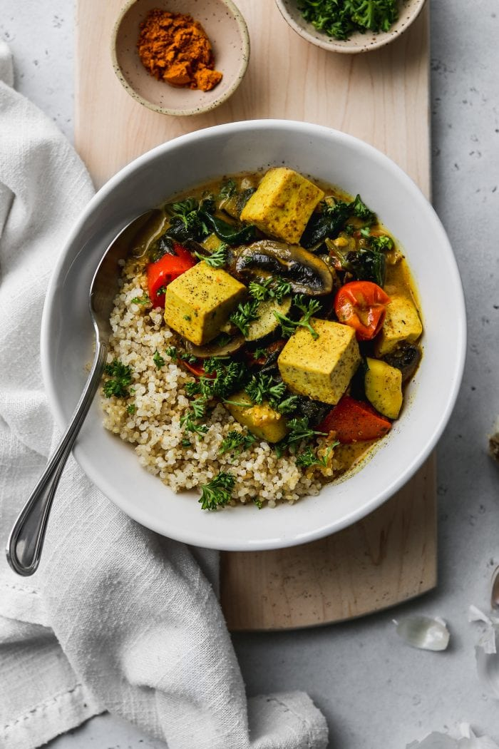 Overhead photo of a white bowl filled with quinoa, tofu, vegetables, and coconut curry on a wooden cutting board.