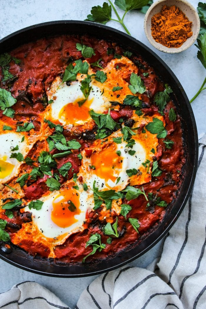 overhead shot of coconut curry shakshuka with runny yolks in a black skillet