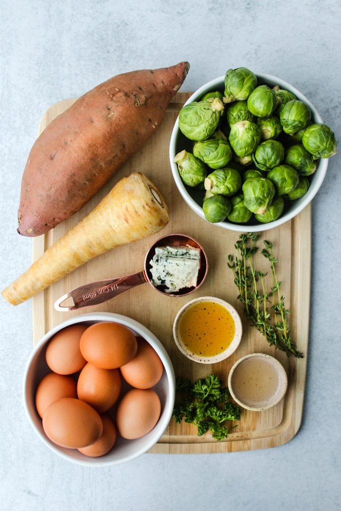 sweet potato, parsnip, brussels sprouts, eggs, oils, herbs on wooden cutting board