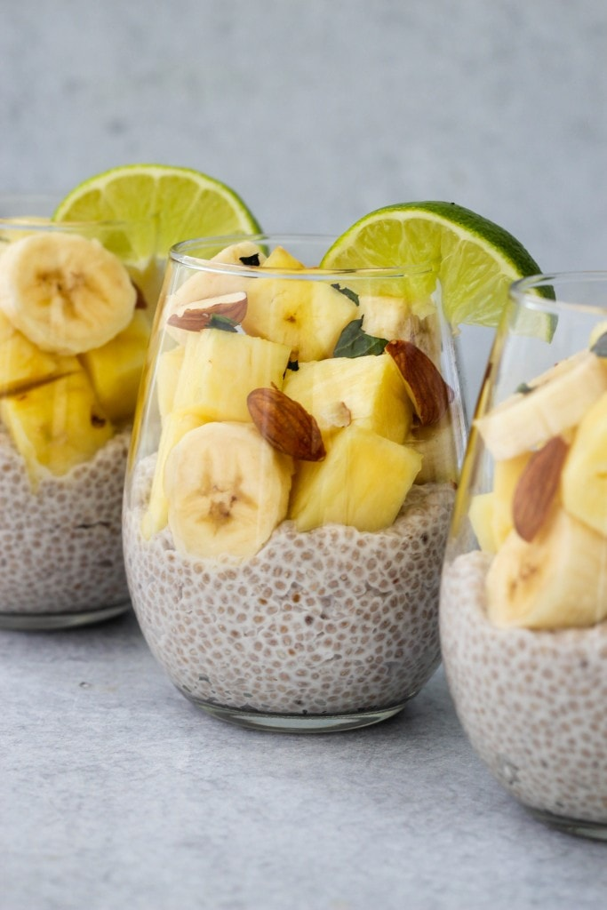 3 glass jars with coconut chia pudding, banana and pineapple slices, chopped almonds and lime