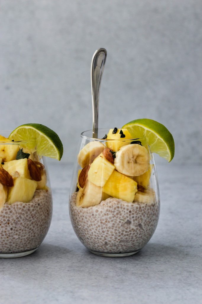 glass jar with silver spoon and coconut chia pudding, banana and pineapple slices, chopped almonds and lime
