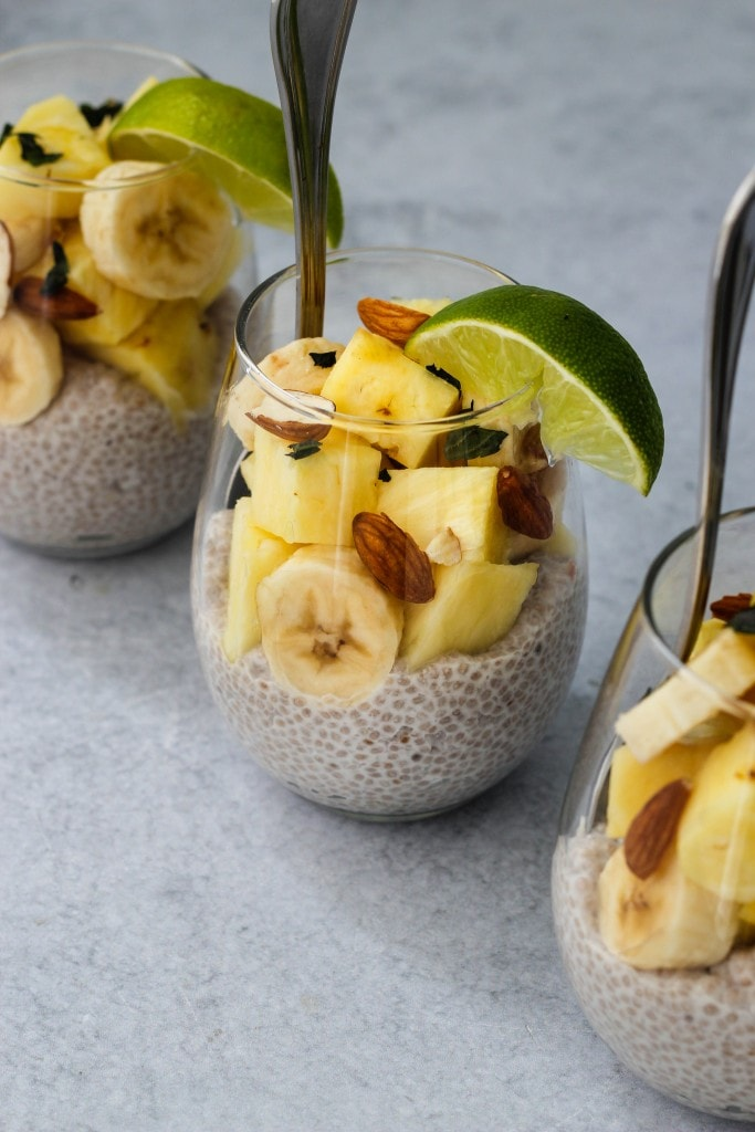 3 glass jars with silver spoons, coconut chia pudding, banana and pineapple slices, chopped almonds and lime