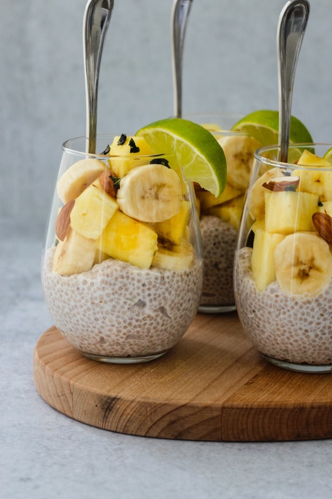 3 glass jars with coconut chia pudding, banana and pineapple slices, chopped almonds and lime on wooden cutting board