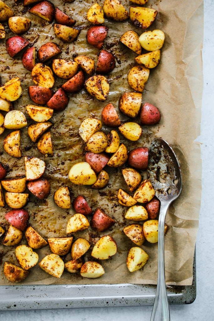 sliced mini potatoes tossed in chili powder and paprika on lined baking sheet