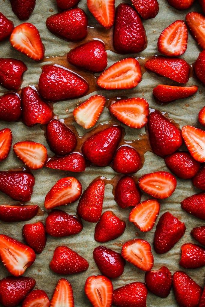 sliced strawberries tossed in honey, vanilla, lemon spread on parchment