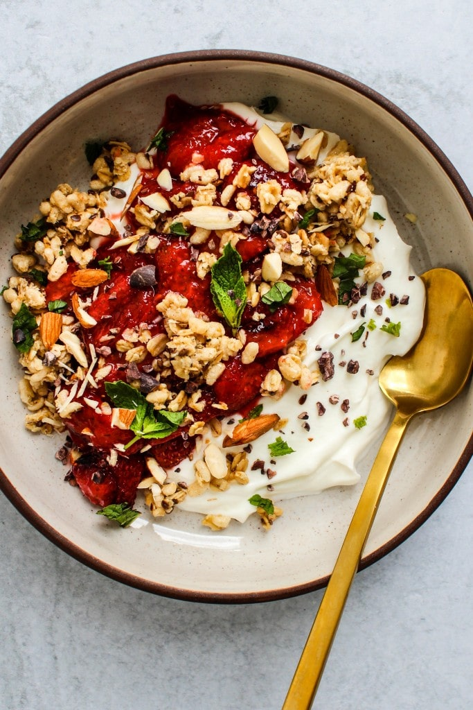 overhead shot of white bowl with greek yogurt, roasted strawberries, granola, mint, gold spoon