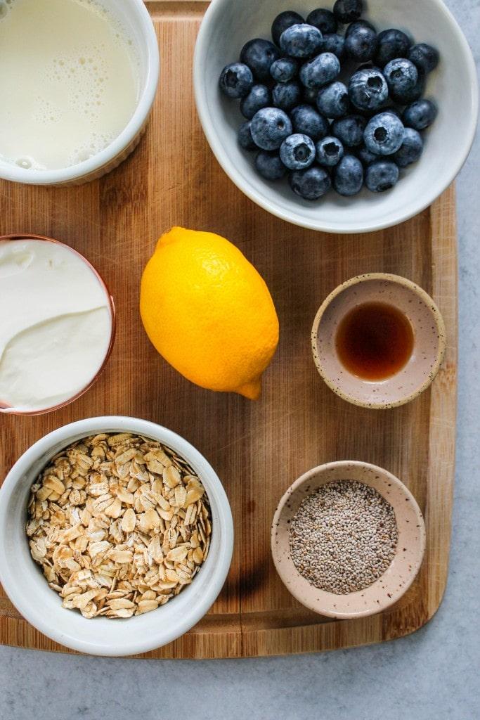 wood cutting board with bowls of blueberries, oats, yogurt, chia seeds, milk, vanilla, and lemon