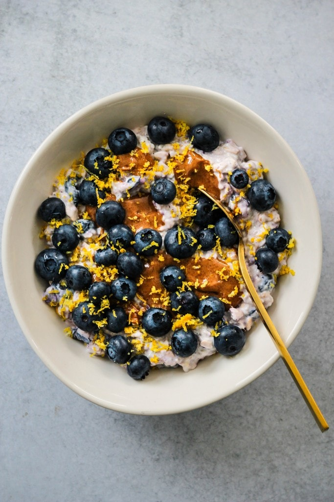 overhead shot of white bowl with overnight oats, blueberries, lemon zest, almond butter and gold spoon