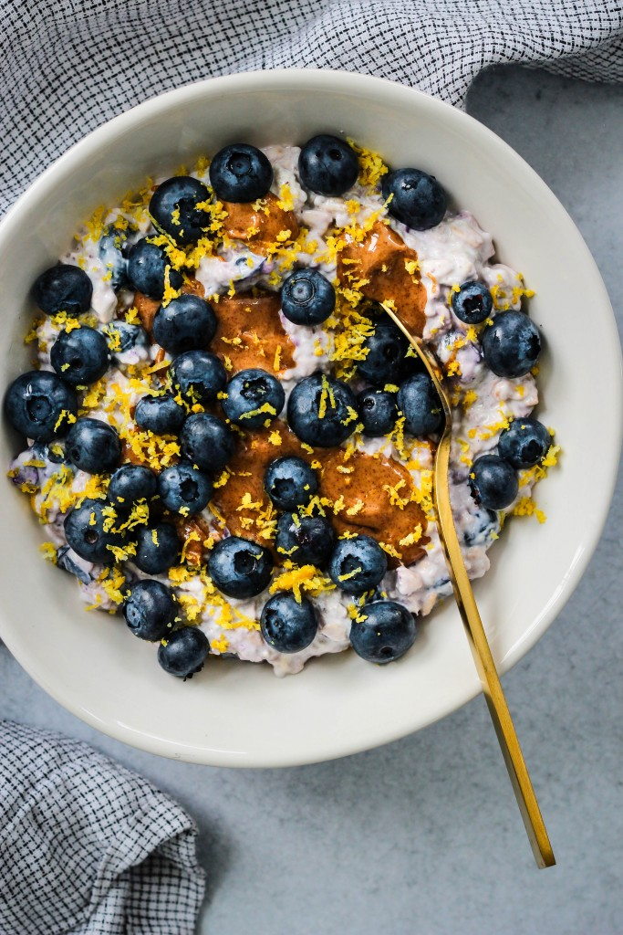 overhead shot of white bowl with overnight oats, blueberries, lemon zest, almond butter and gold spoon with blue towel