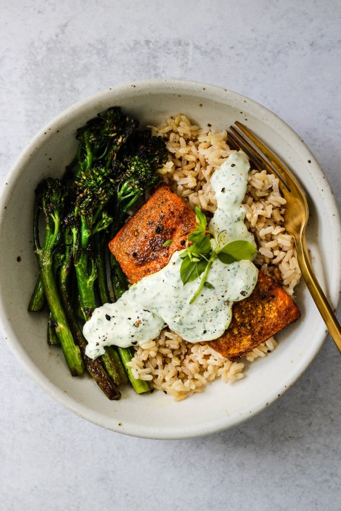 overhead shot of white bowl with broccolini, brown rice, turmeric salmon, parsley yogurt sauce