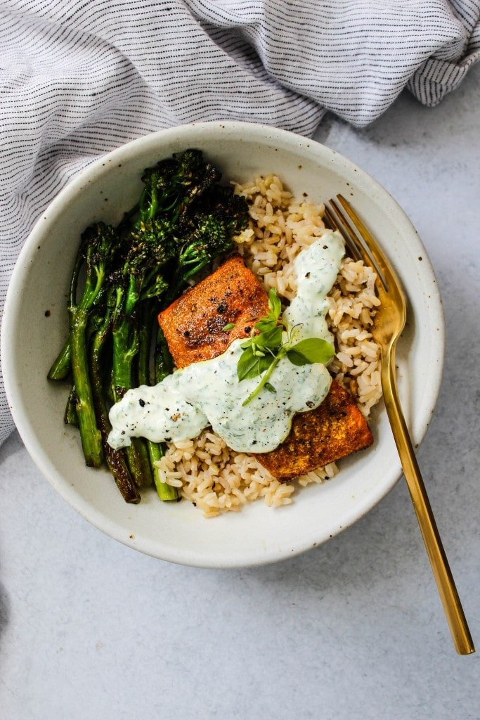 overhead shot of white bowl with broccolini, brown rice, turmeric salmon, parsley yogurt sauce and blue towel