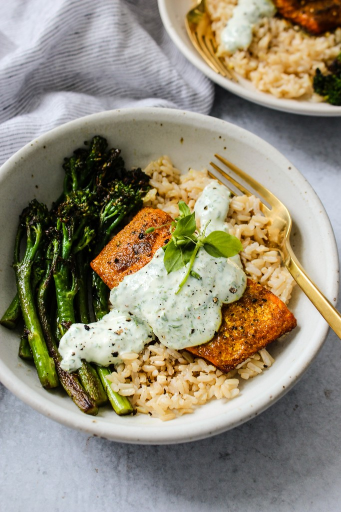 side angle shot of white bowl with broccolini, brown rice, turmeric salmon, parsley yogurt sauce