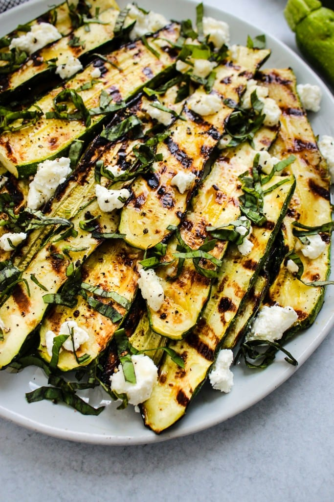 light blue plate with grilled zucchini slices topped with crumbled goat cheese, basil and honey