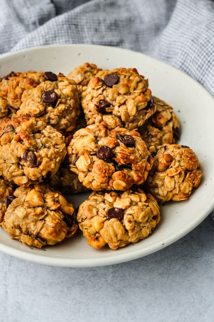 side angle of white bowl with tahini oatmeal chocolate chip cookies