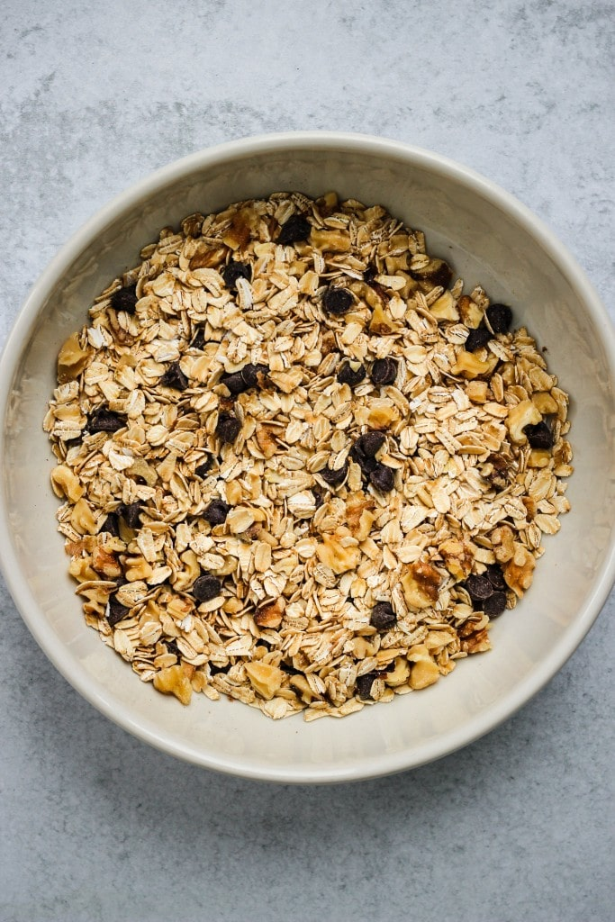 large white bowl with rolled oats, walnuts, and chocolate chips