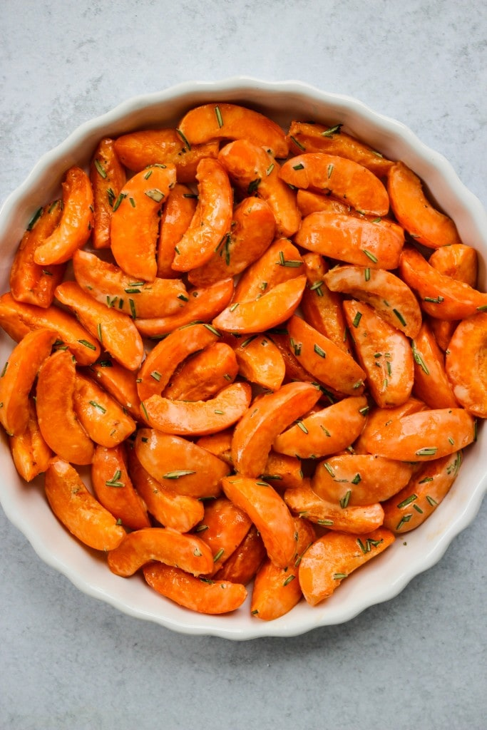 sliced apricots and rosemary in white baking dish