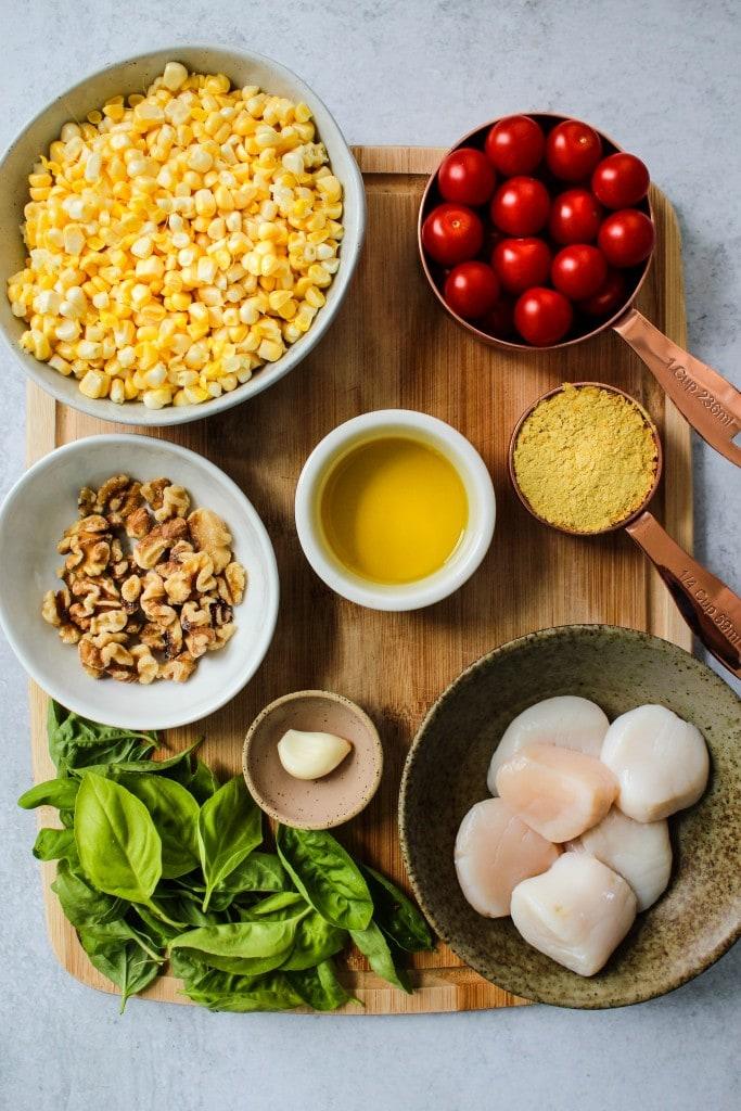 wood cutting board with bowls of corn, tomatoes, walnuts, scallops, basil