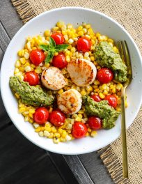 overhead shot of white bowl with bed of corn and cherry tomatoes topped with seared scallops and pesto