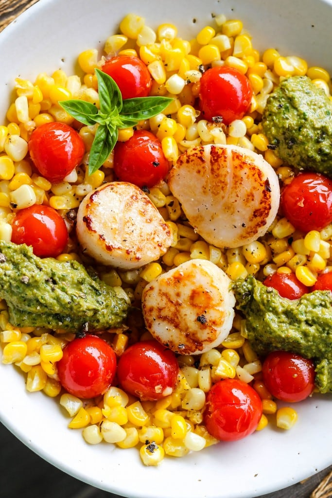 closeup shot of white bowl with bed of corn and cherry tomatoes topped with seared scallops and pesto