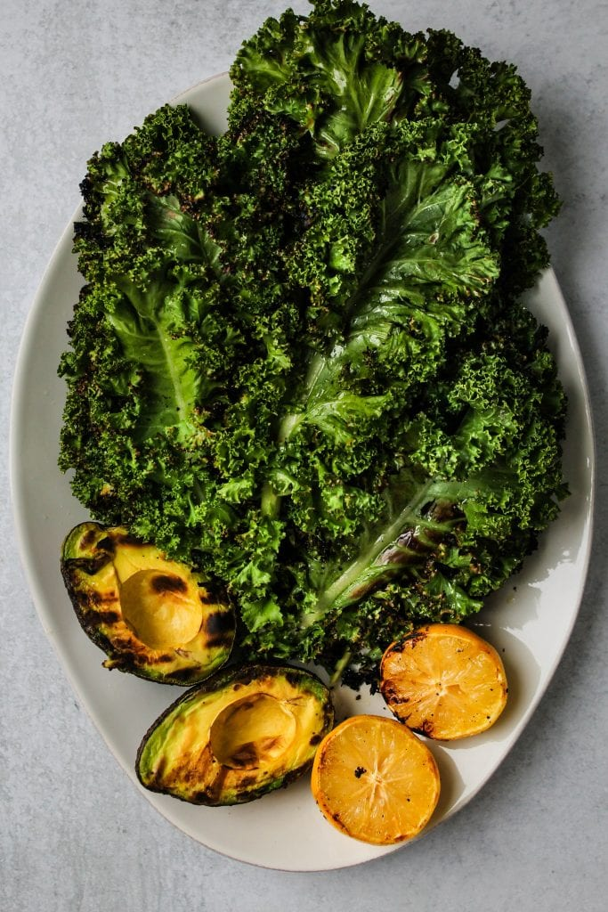 white plate with grilled kale, avocado, and lemon