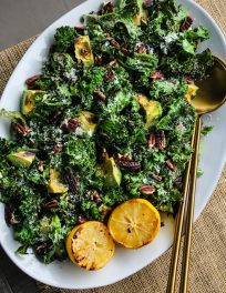 overhead shot white serving plate with grilled kale salad topped with avocado, pecans, parmesan, lemons