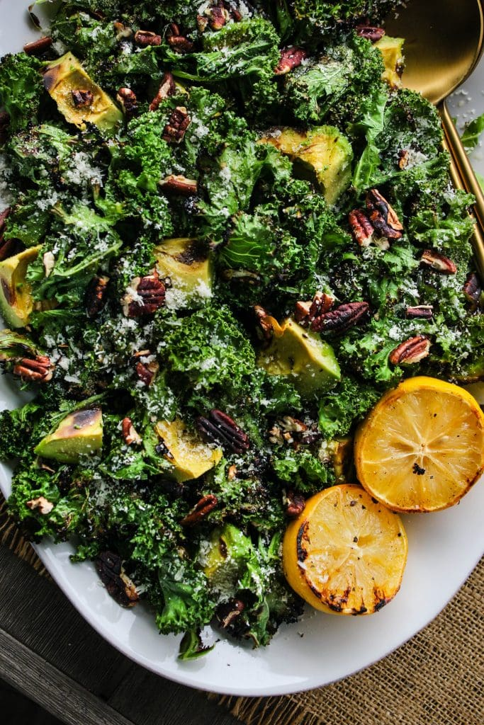 white serving plate with grilled kale salad topped with avocado, pecans, parmesan, lemons