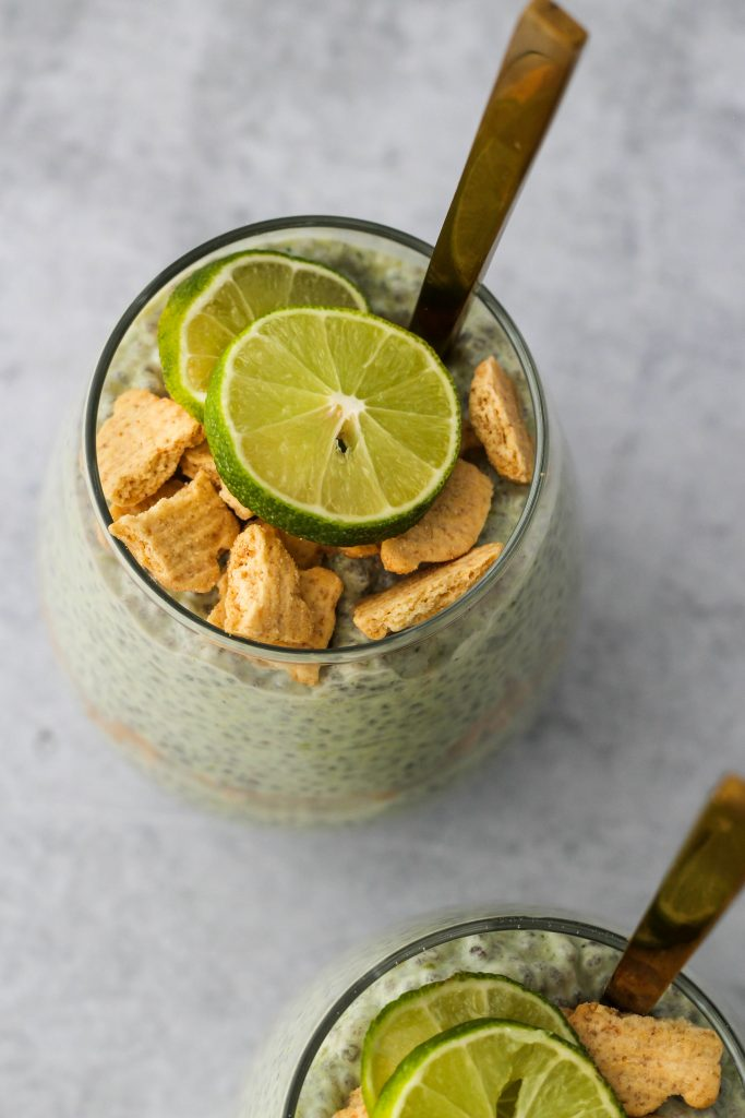 overhead shot of glass jar with chia pudding, lime slices, and graham crackers
