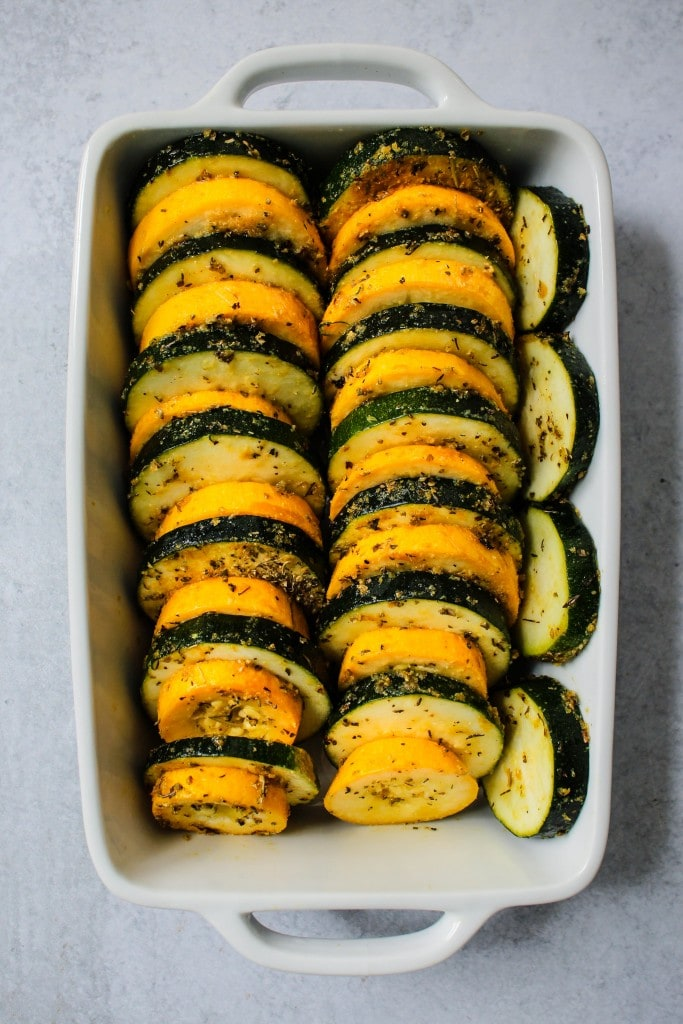 white casserole dish with sliced rounds of green and yellow zucchini lined up
