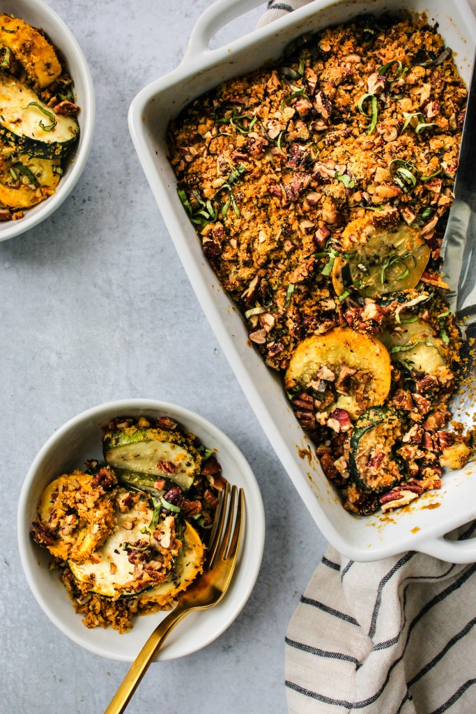 overhead shot of white casserole dish with baked zucchini squash casserole with pecan parm served in small white bowls