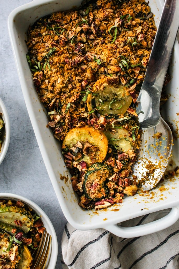 close up shot of white casserole dish with baked zucchini squash casserole with pecan parm served in small white bowls