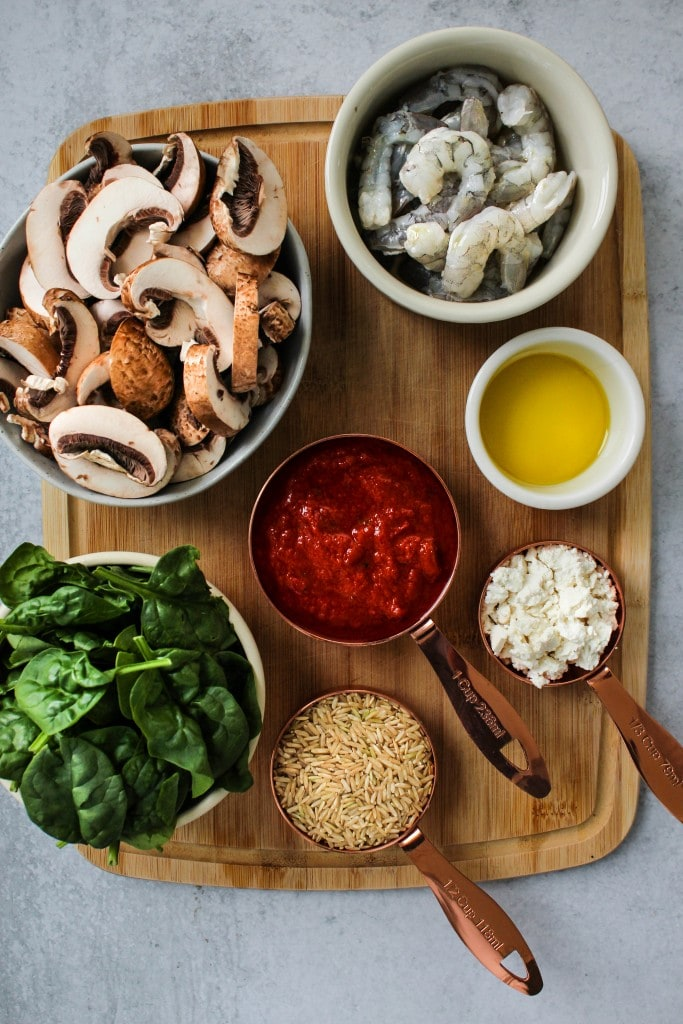 wood cutting board with bowls of mushrooms, spinach, shrimp, tomato sauce, rice, feta, and olive oil