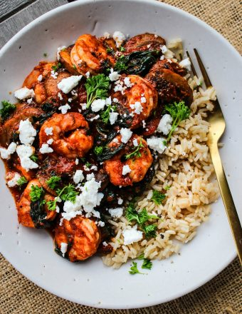 white bowl with sauteed shrimp, tomato sauce,vegetables, feta, parsley over brown rice with gold fork